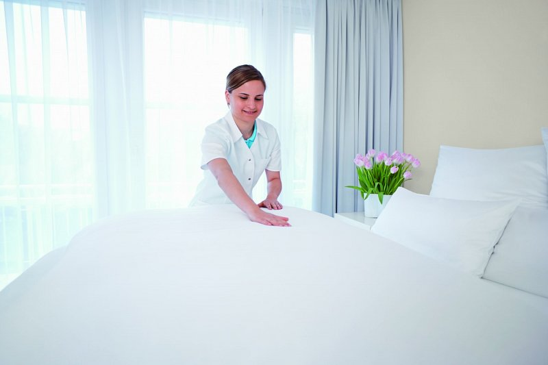 Care Home Making Bed with Clean Laundered Linen
